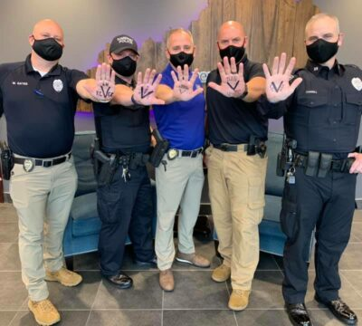 police officers holding hands up with V written on them