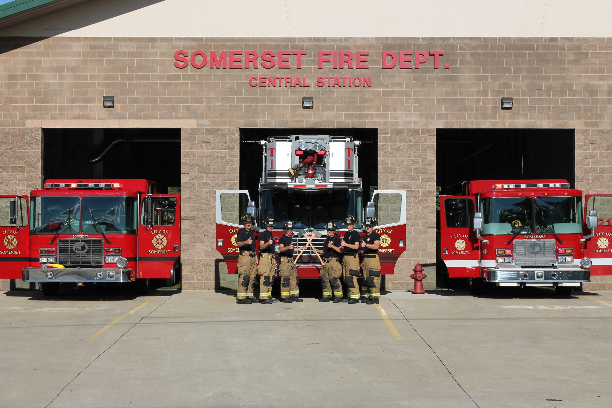 firemen standing in front of fire trucks at station