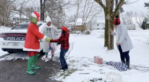 The Grinch dancing in the snow with young girl and her mother
