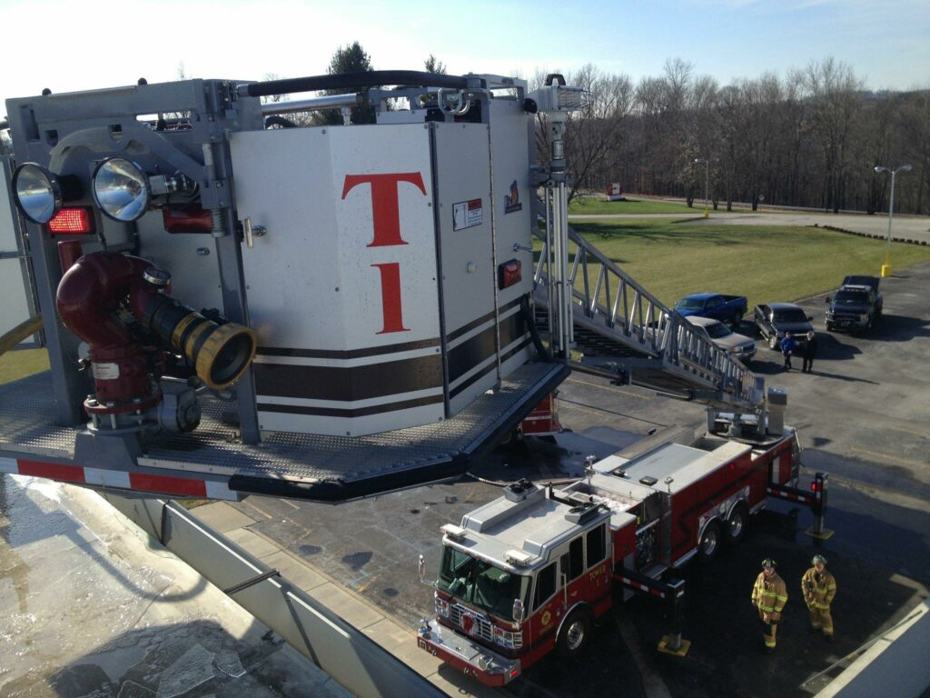 Aerial view of fire truck from bucket with firemen standing below