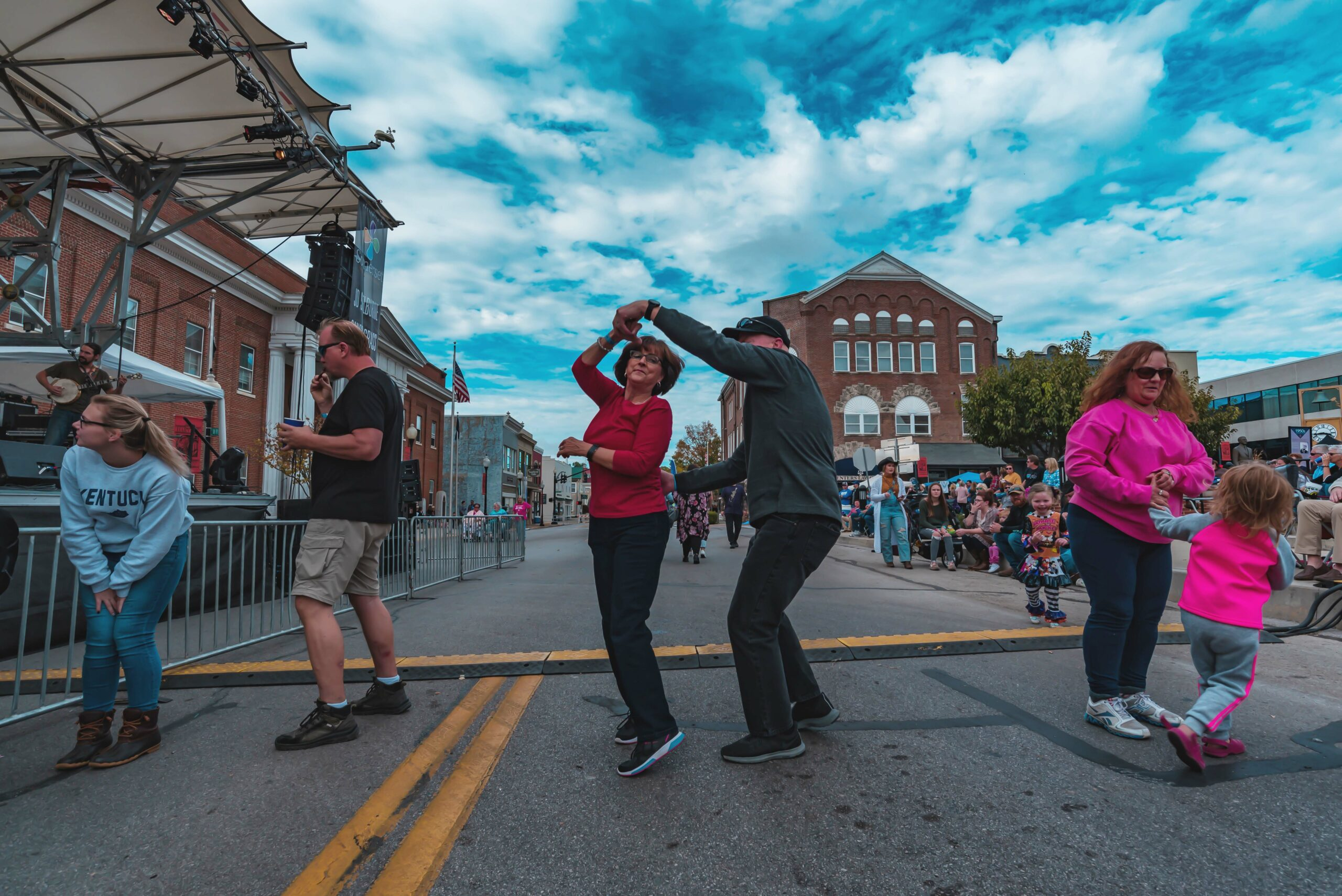 man twirling woman in the middle of street during festival