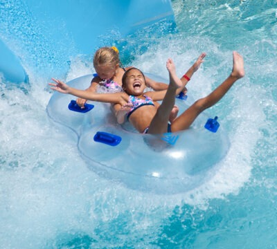 girls sliding down waterslide on a tube