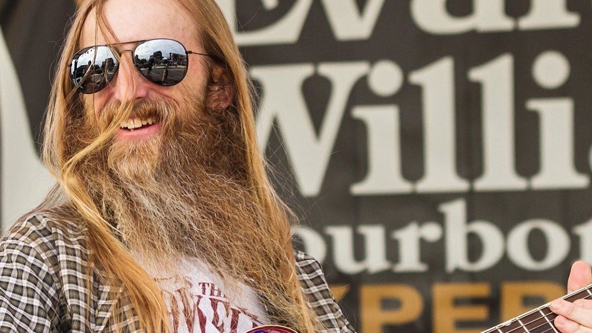 Man with long hair and beard playing guitar