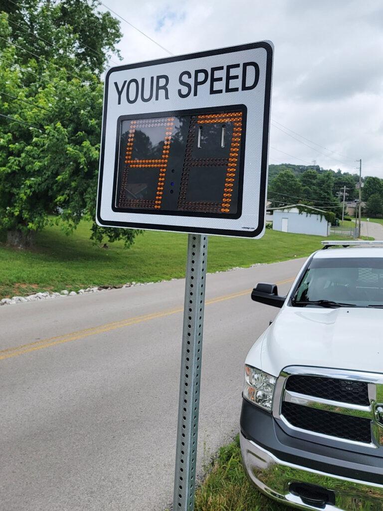 police car on side of road behind radar sign