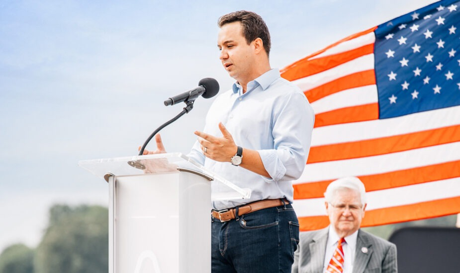 man standing at podium speaking with American flag in the background